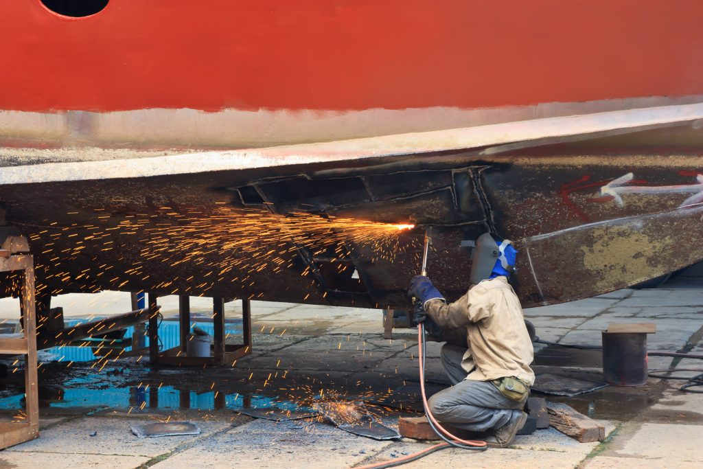 Man welding a boat, manufacturing